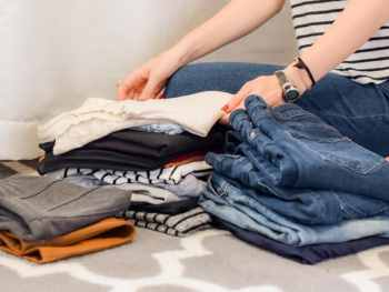 woman folding clothes for capsule wardrobe