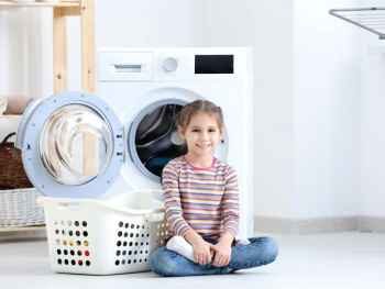 Little girl helping with laundry at home