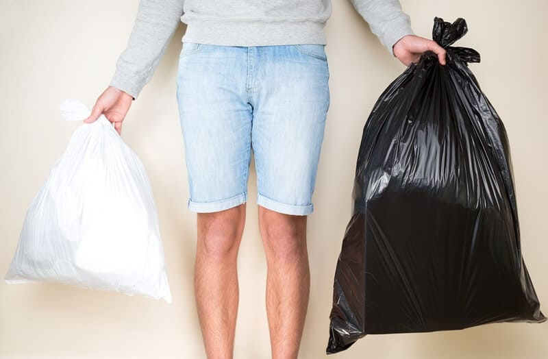 Young man holding two garbage bags.