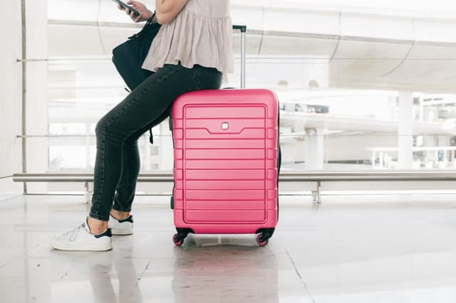 Pink carry on luggage with a girl sitting on top of it at the airport