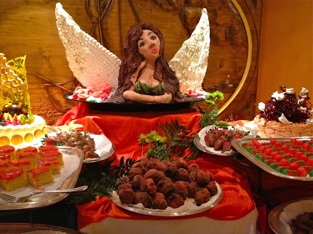 Dessert buffet with an angel marzipan sculture and lots of desserts