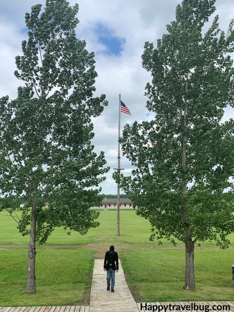 Soldier standing between two large trees with the American Flag in between