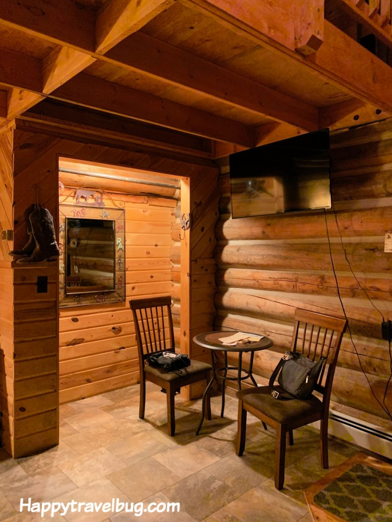 table and 2 chairs in log cabin