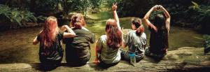 five girls sitting on log over creek