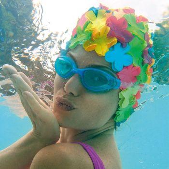 Woman wears a colorful petal swim cap underwater