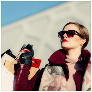 Girl with sunglasses outdoors holding several bags while shopping