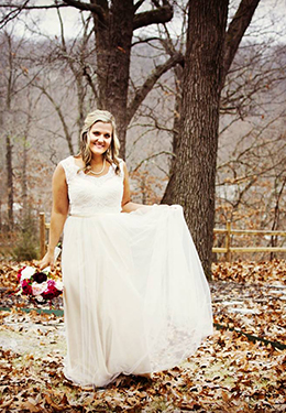 Bride white gown with red and white bouquet standing amidst leaves in a country landscape with trees and woods background.