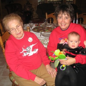 Three generations of ladies: a grandmother, mother and small baby sitting at a table