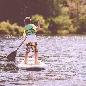 Bright sunny day with a young boy in colorful shorts out on the water paddleboarding