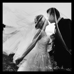 Black and white image of bride and groom outside by water - image by hisu-lee www.unsplash.com