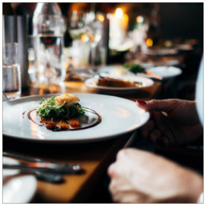 Several white plates with gourmet food on a table - image by jay wennington unsplash.com