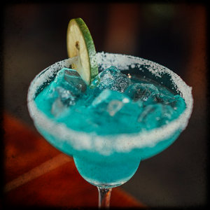 Cocktail glass with blue cocktail, lime wedge and sugar around the rim