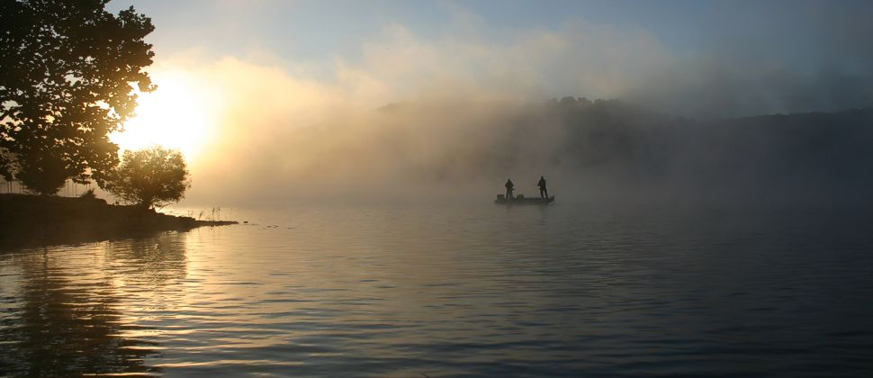 Two people fishing from boat on foggy clam lake at sunrise