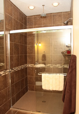 Brown tiled large shower with glass doors and brown towel with overhead lighting
