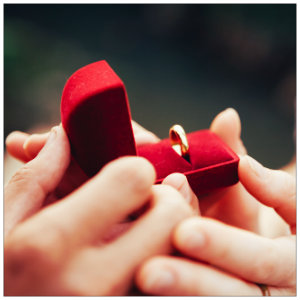 Two hands holding an open red velvet box with a gold ring inside