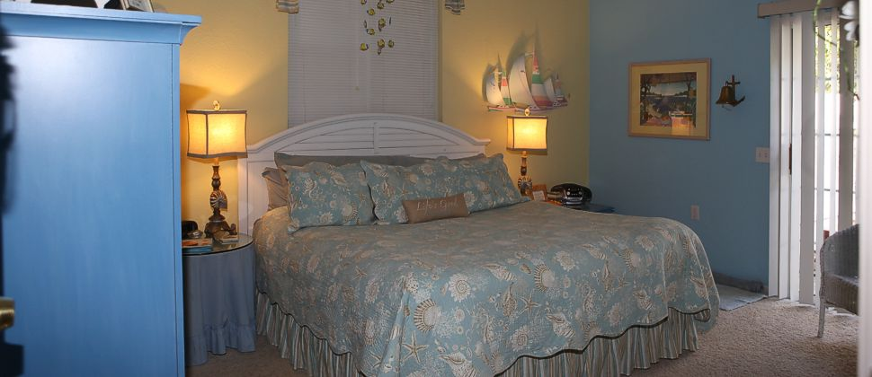 Blue and yellow walled room with large white bed with blue soft bedding and nautical decor