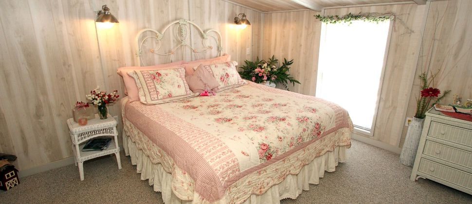 Light and airy white paneled room with pink and white bedding on white iron bed