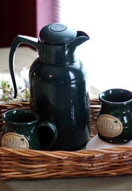 Deep Dark green stoneware mugs and green coffee pot on wicker tray