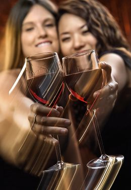 Two ladies with brown hair are smiling and clinking wine glasses with red wine