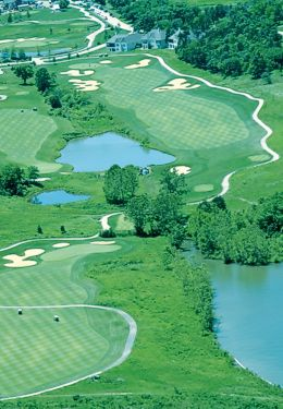 Overhead view of a bright green golf course with path winding through greens and water features