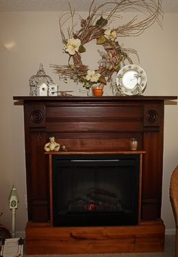 Wooden framed fireplace with floral wall aer and country style decorations on mantel
