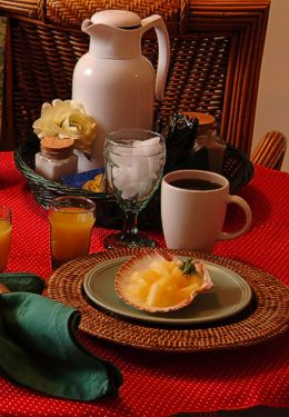 Place setting on red tablecloth with coffee and fruit in shell on green plate