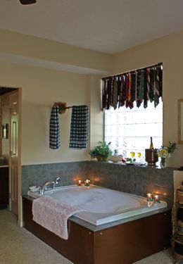 Large Guest bathroom with tub for two with lit candles and cream walls