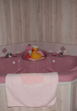 Pink two person Tubbie with rubber ducky and white wood paneling