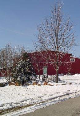 Large red barn structure in snow on sunny day with bare trees
