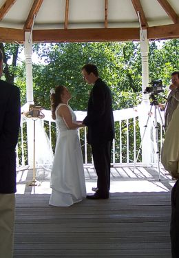 Bride dressed in a beautiful white gown and Groom all in black stand gazing at one another in sunlit gazebo.