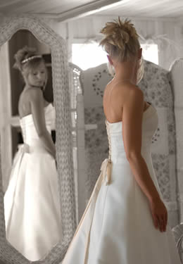Blonde bride looking at back of wedding gown while reflected in white wicker mirros