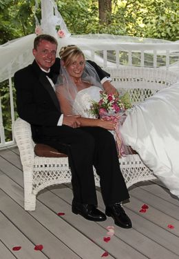 Bride and Groom lounging on white wicker patio furniture.