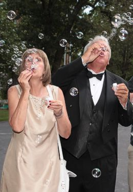 Wedding guests in black tuxedo and taupe gownblowing bubbles at after ceremony.