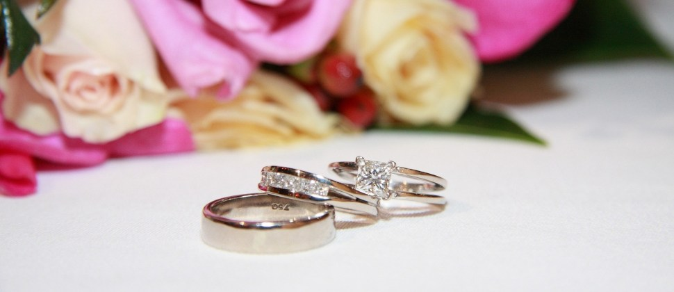 A set of sparkling diamond wedding rings on a white table with white and pink roses in the background