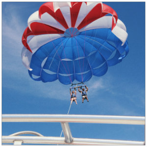 Red, white and blue parasail with two people strapped in below - Image by AJ Garcia on Unsplash