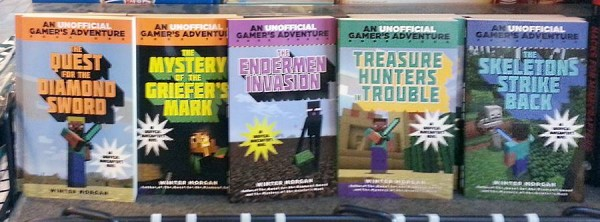 "Image taken at a bookfair, depicting several unlicensed paperback Minecraft novels. Titles going left-to-right: ""The Quest for the Diamond Sword"", ""The Mystery of the Griefer's Mark"", ""The Endermen Invasion"", ""Treasure Hunters Trouble"", and ""The Skeletons Strike Back"". All books carry the stamp, ""An UNOFFICIAL Gamer's Adventure,"" with the word ""unofficial"" given special visual emphasis."