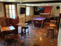The bar side of the pub with dartboard and pool table