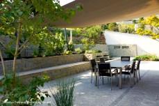 grosszügiger Sitzplatz mit Sonnensegel im Terrassengarten