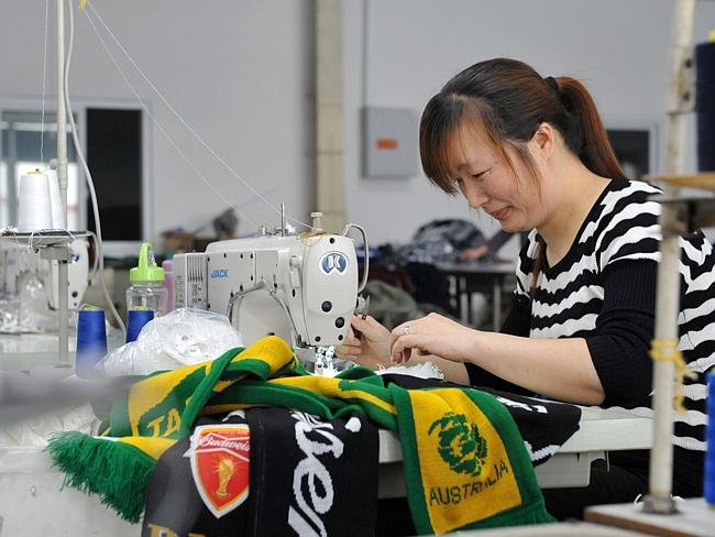 Factory ... A factory worker makes Australia scarves for the 2014 FIFA World Cup