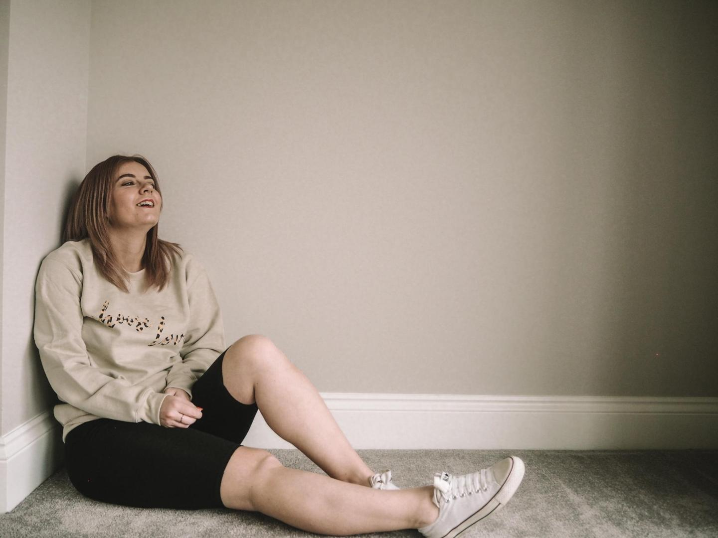 Emma aka Harmony Blaze relaxing. She is wearing a beige 'choose love' sweater, black cycling shorts and white converse.