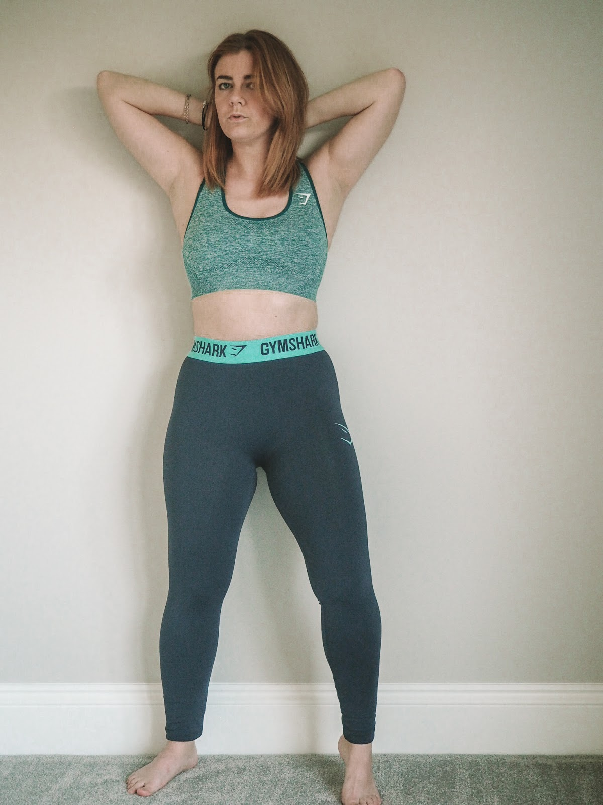 Emma standing against a plain grey wall in a teal sports bra and navy leggings with her hands behind her head