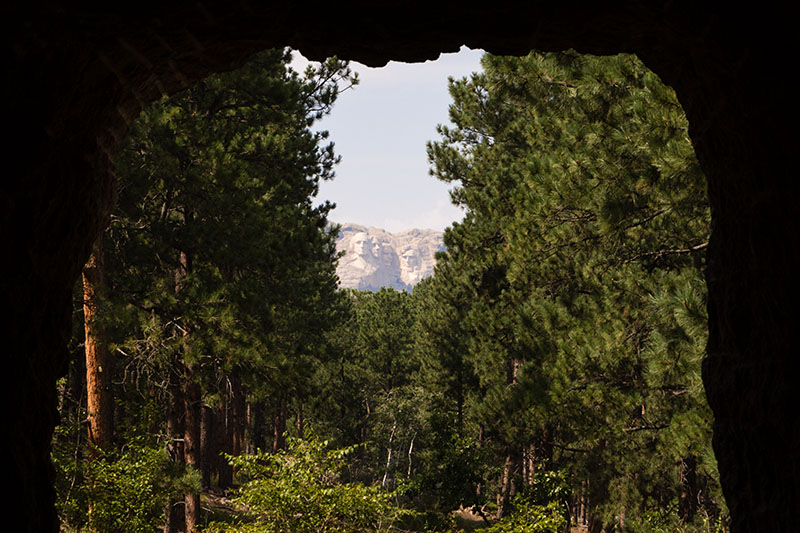 Mount Rushmore viewed through a tunnel on a near-by road.