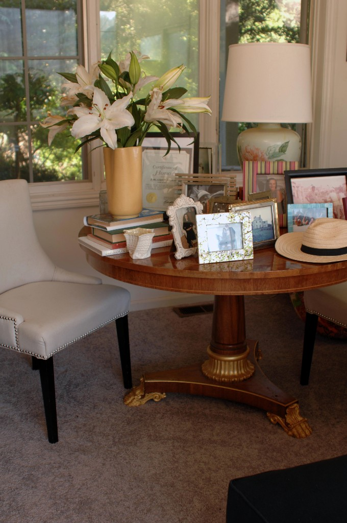 cream chair and antique table with decor and mementos