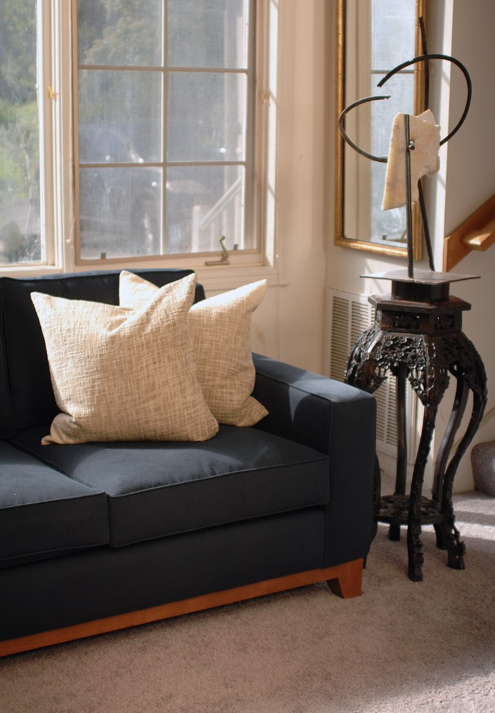 navy blue sofa with two white decorative pillows in a living room