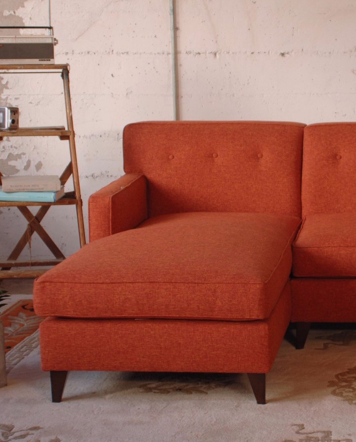orange sectional sofa on a patterned rug