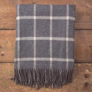grey and white windowpane patterned blanket with tassels