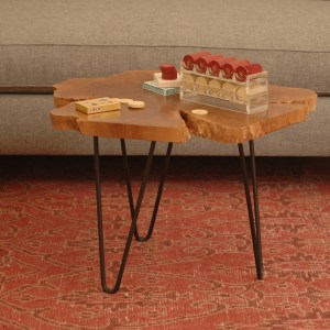 raw edge wood and steel coffee table on a red rug
