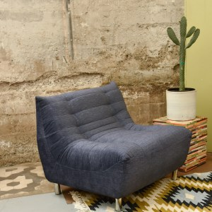 grey accent chair in a living room with decor