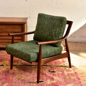 Green mid century modern style armchair in a living room