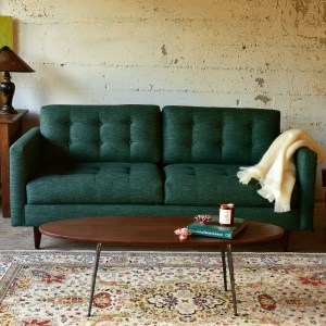 Green mid century modern style sofa in a living room with decor
